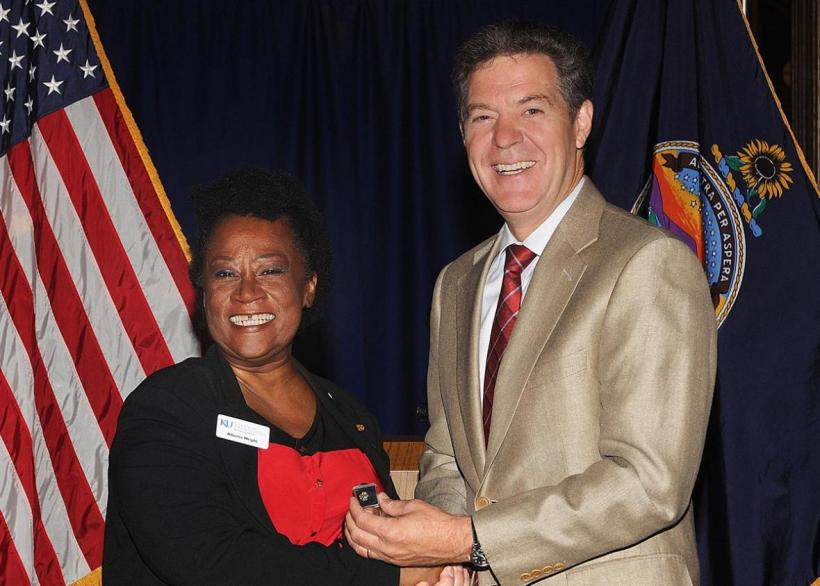 Alberta Wright accepting a service award from Governor Brownback