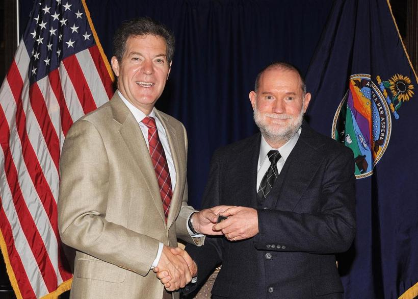 Malcom Neely accepting a service award from Governor Brownback